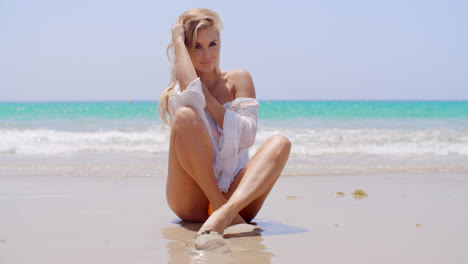 Seductive-Young-Woman-Sitting-on-the-Beach-Sand