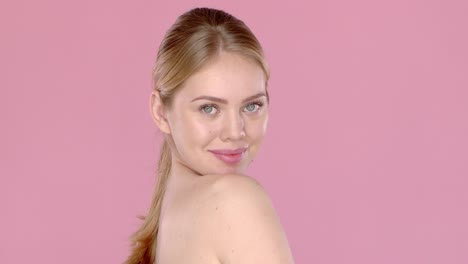 Slow-motion-video-shot-of-happy-beautiful-girl-isolated-on-pink-background-Side-angle