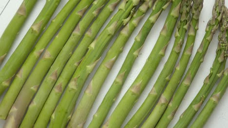 Green-fresh-and-healrhy-asparagus-placed-on-a-white-wooden-table-Top-view-Close-up-
