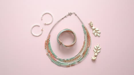 Woman-fashion-accessories-Jewelry-Earings-and-necklace-on-stylish-pastel-pink-background-Flat-lay