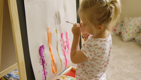 Little-girl-standing-painting-at-an-easel