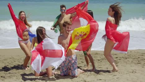 Group-of-Friends-in-Swim-Suits-with-Flags-at-Beach