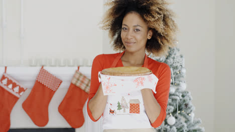 Happy-young-woman-holding-a-Christmas-pastry