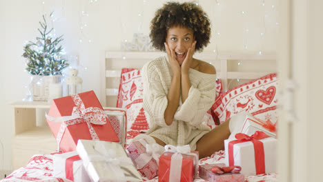 Excited-young-woman-with-a-bed-full-of-Xmas-gifts