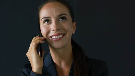 Businesswoman-speaking-on-phone-and-looking-up