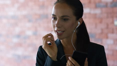 Young-businesswoman-talking-on-phone-with-earphones
