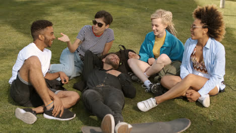 Cool-young-friends-chilling-on-meadow