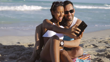 Happy-diverse-couple-taking-selfie-on-beach