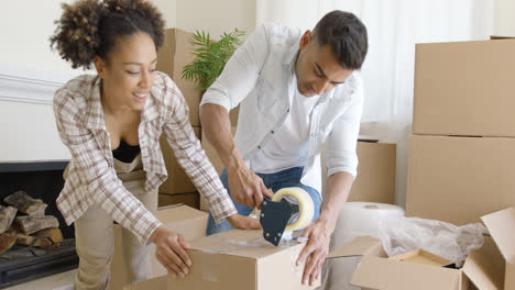 Couple-taping-boxes-as-they-pack-up-their-home