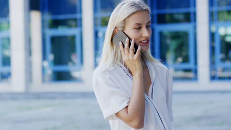 Young-woman-speaking-on-phone-near-building