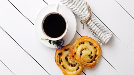 Delicious-pastry-with-raisins-and-a-cup-of-coffee-top-view-