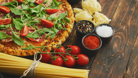 Italian-food-background-with-pizza-raw-pasta-and-vegetables-on-wooden-table
