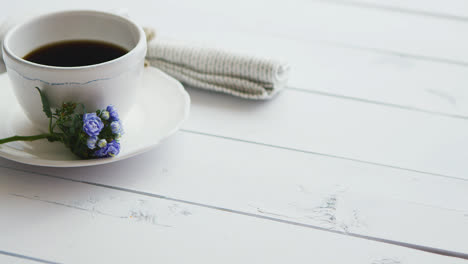 Black-coffee-in-white-cup-on-bright-wooden-background