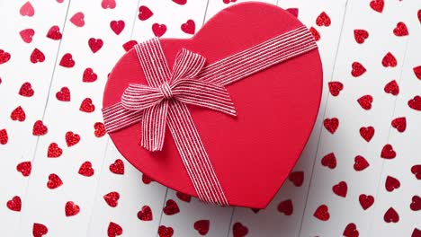 Boxed-gift-placed-on-heart-shaped-red-sequins-on-white-wooden-table