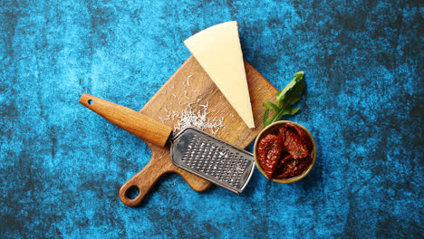 Grated-parmesan-cheese-and-metal-classic-grater-placed-on-wooden-cutting-board