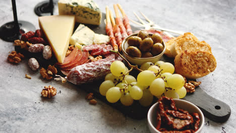 Cold-snacks-board-with-meats-grapes-wine-various-kinds-of-cheese