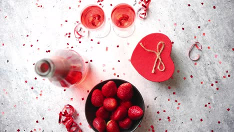 Bottle-of-rose-champagne-glasses-with-fresh-strawberries-and-heart-shaped-gift