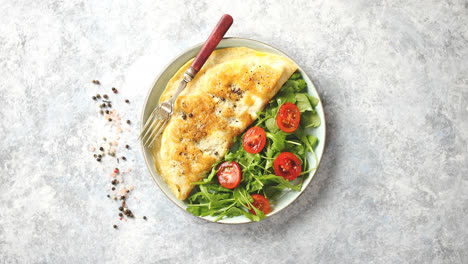 Classic-egg-omelette-served-with-cherry-tomato-and-arugula-salad-on-side