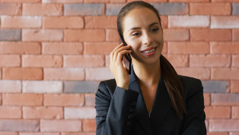 Smiling-businesswoman-with-ponytail-speaking-on-smartphone