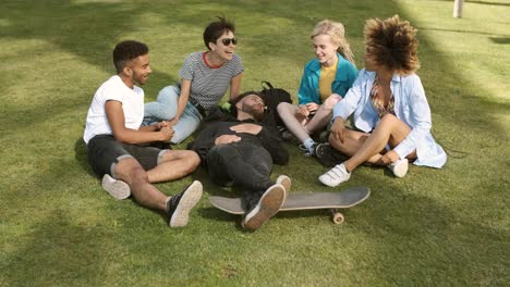 Lounging-friends-on-meadow-in-park