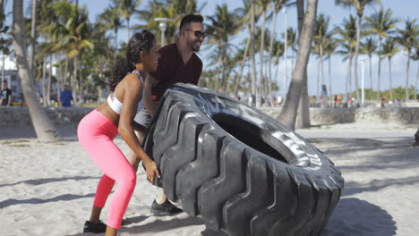 Sporty-couple-training-with-tyre-together