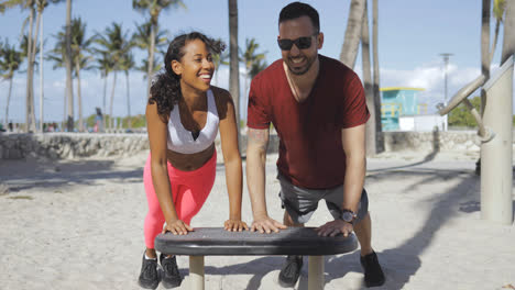Laughing-sporty-couple-training-in-beach-gym-