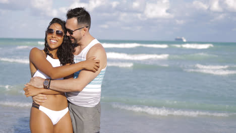Beautiful-diverse-couple-embracing-on-beach