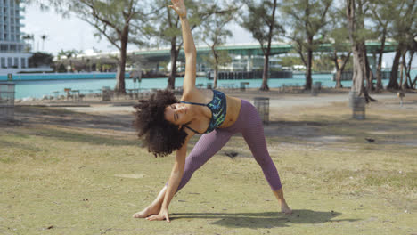 Black-sporty-girl-training-asana-on-lawn