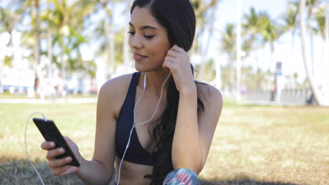 Sporty-woman-listening-to-music-in-park