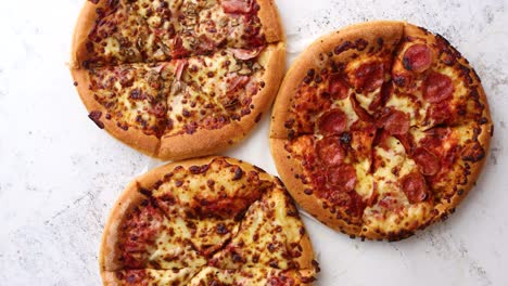 Three-american-style-pizzas-served-on-a-table