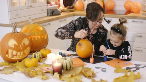 Woman-and-girl-painting-face-on-pumpkin