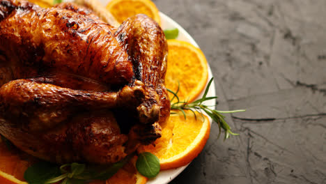 Roasted-whole-chicken-or-turkey-served-in-white-ceramic-plate-with-oranges