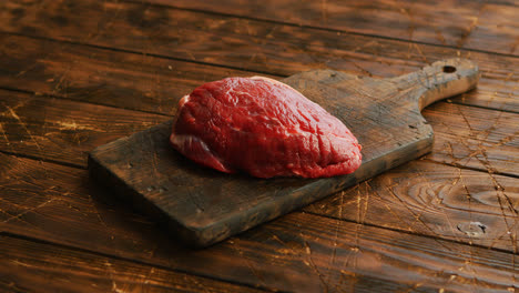Big-fresh-piece-of-meat-laid-on-wooden-cutting-board