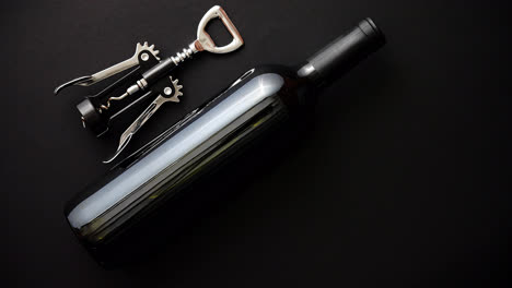 Red-wine-bottle-and-corkscrew-on-black-matte-background-