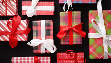 Top-view-of-wrapped-Christmas-presents-laid-on-the-black-background