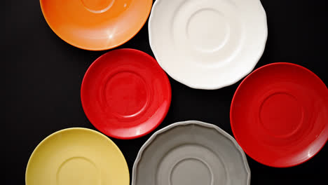 Colorful-empty-plates-and-saucers-over-black-background-