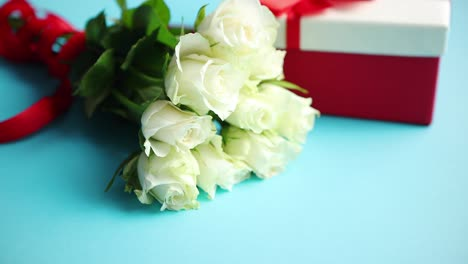 Bouquet-of-white-roses-with-red-bow-on-blue-background-Boxed-gift-on-side