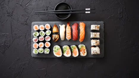 Sushi-rolls-set-with-salmon-and-tuna-fish-served-on-black-stone-board