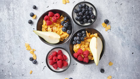 Golden-cornflakes-with-fresh-fruits-of-raspberries-blueberries-and-pear-in-ceramic-bowl