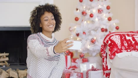 Happy-young-woman-posing-for-a-Christmas-selfie