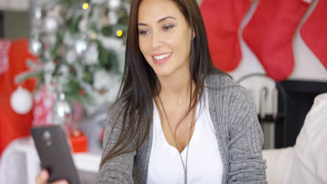 Smiling-young-woman-checking-Christmas-messages