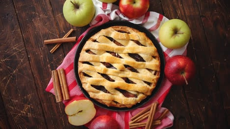 Homemade-pastry-apple-pie-with-bakery-products-on-dark-wooden-kitchen-table