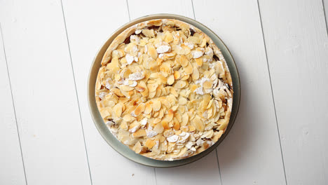 Freshly-baked-homemade-apple-pie-with-almond-flakes-cake-on-yellow