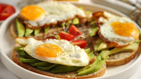 Close-up-of-healthy-breakfast-with-sliced-avocado-sandwiches-with-fried-egg