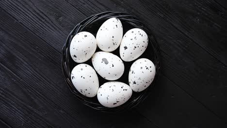 Whole-Chicken-eggs-in-a-nest-on-a-black-rustic-wooden-background--Easter-symbols