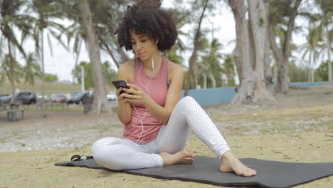 Chilling-young-womanl-using-phone-on-mat