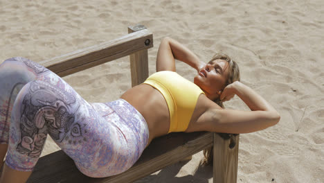 Concentrated-woman-training-abs-on-beach