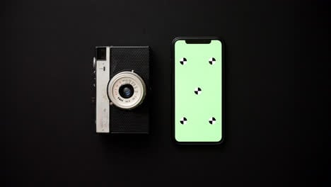 Old-retro-film-camera-and-modern-smartphone-on-black-background