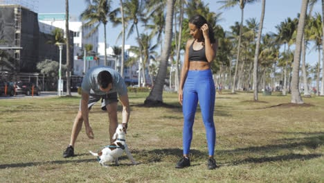 Sporty-couple-with-dog-in-park