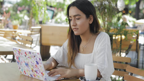 Woman-sitting-working-at-an-outdoor-cafeteria